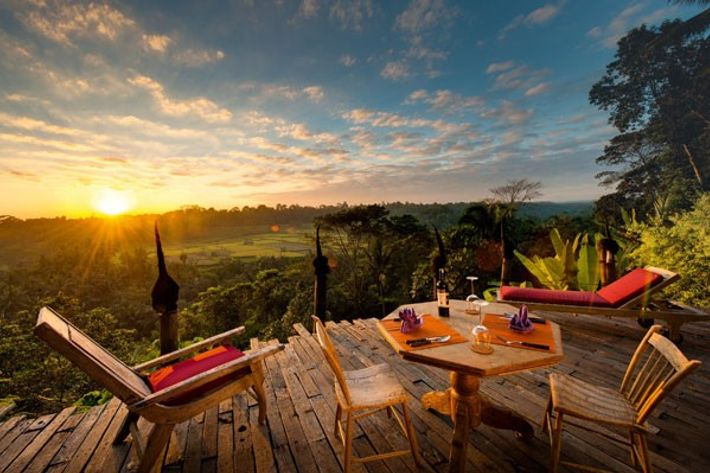 Table and chairs on a wooden deck at Bambu Indah in Ubud, Bali at sunset