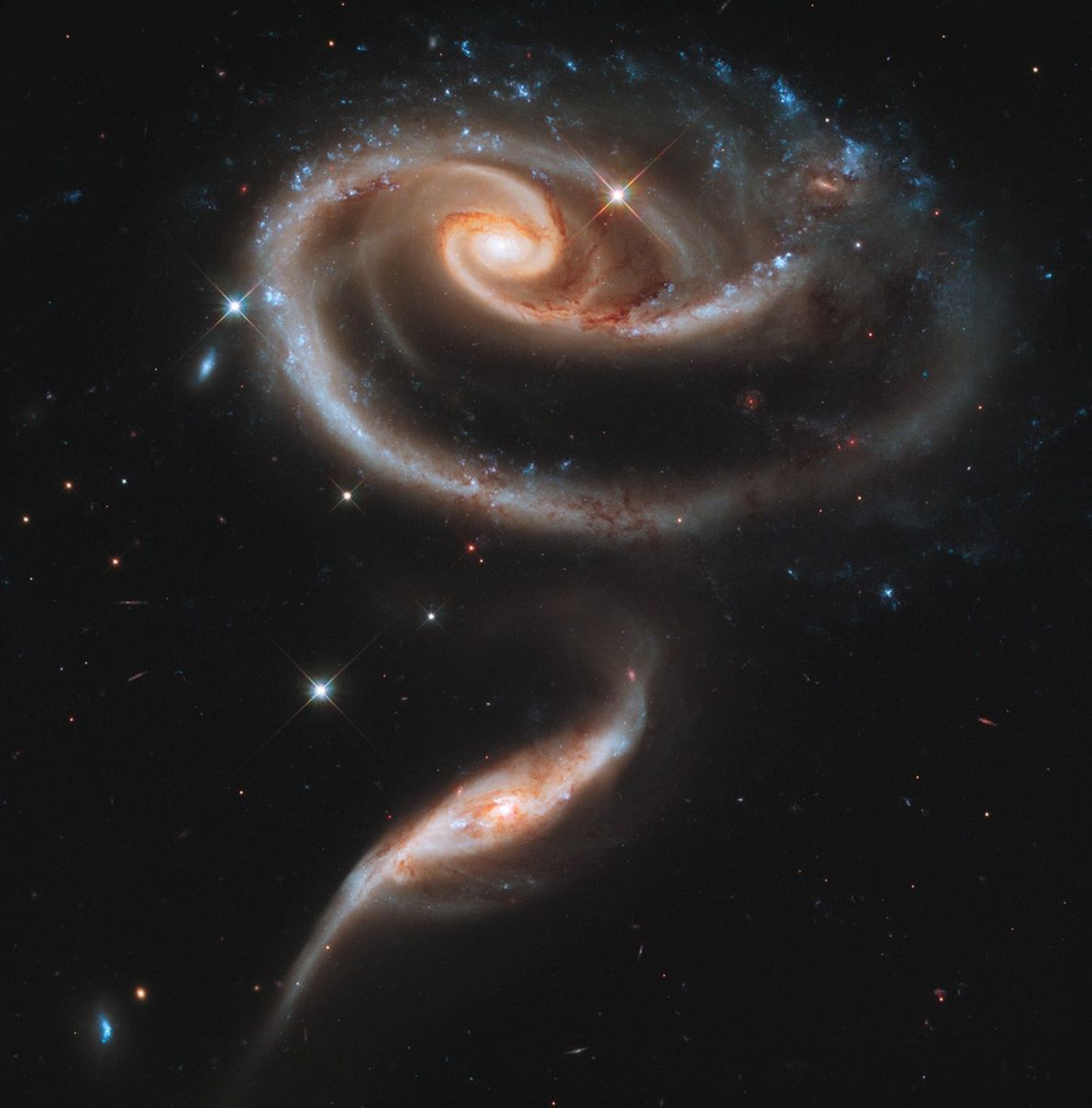 Two spiral galaxies, collectively known as Arp 273, prepare to merge 300 million light-years away.