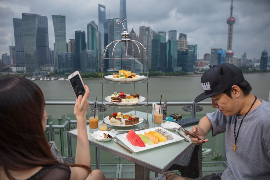 A couple enjoy afternoon tea at a luxury hotel in Shanghai with a view of the ...