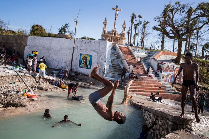 Kids swim in a river where a bridge collapsed in Port Salut, Haiti. The city suffered ...