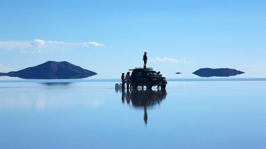 Tourists waiting at sunset in the middle of the Salar de Uyuni, southwest Bolivia, the largest salt ...