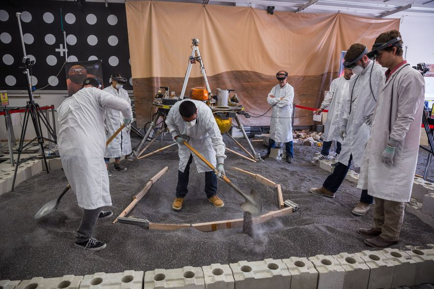 Engineers in the In Situ Instrument Lab dig a trench that corresponds to the augmented-reality landscape ...