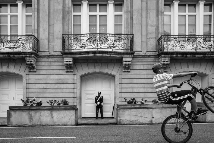 A young cyclist rides past a guard at the presidential palace, the Casa de Nariño.