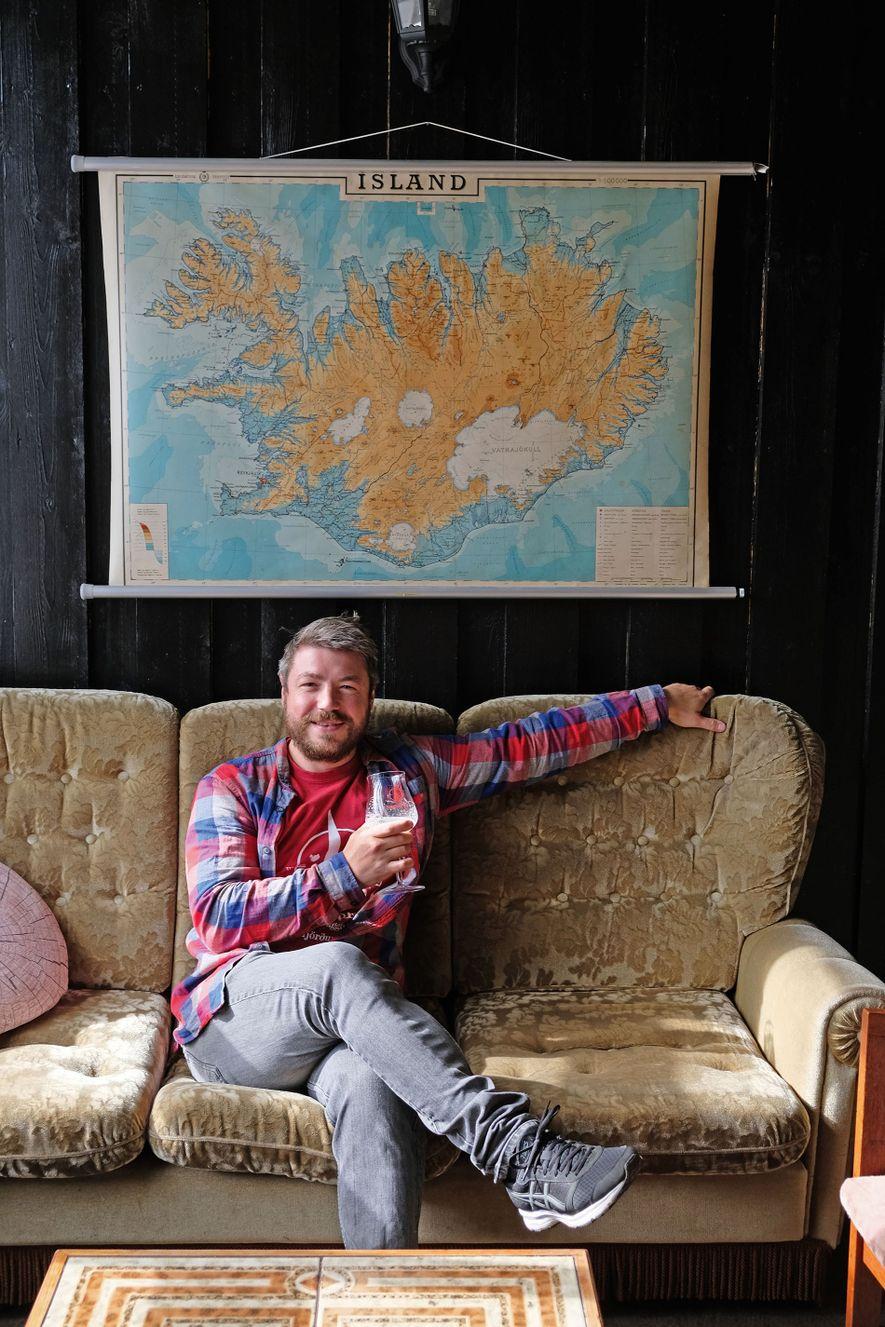 Marteinn Haraldsson, owner of Segull 67 in Siglufjörður, sits in a chair under a map of ...