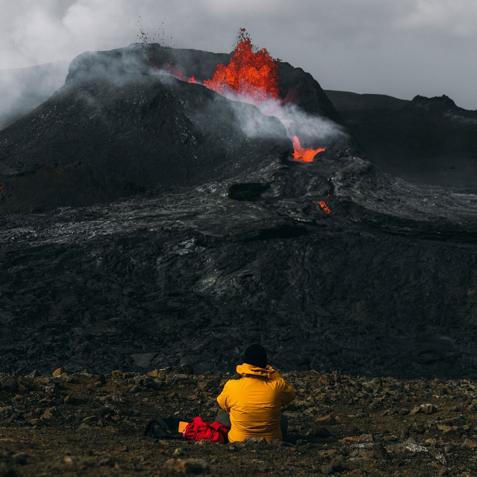 A photographer perches on the edge of a volcano and shoots an eruption from a safe ...