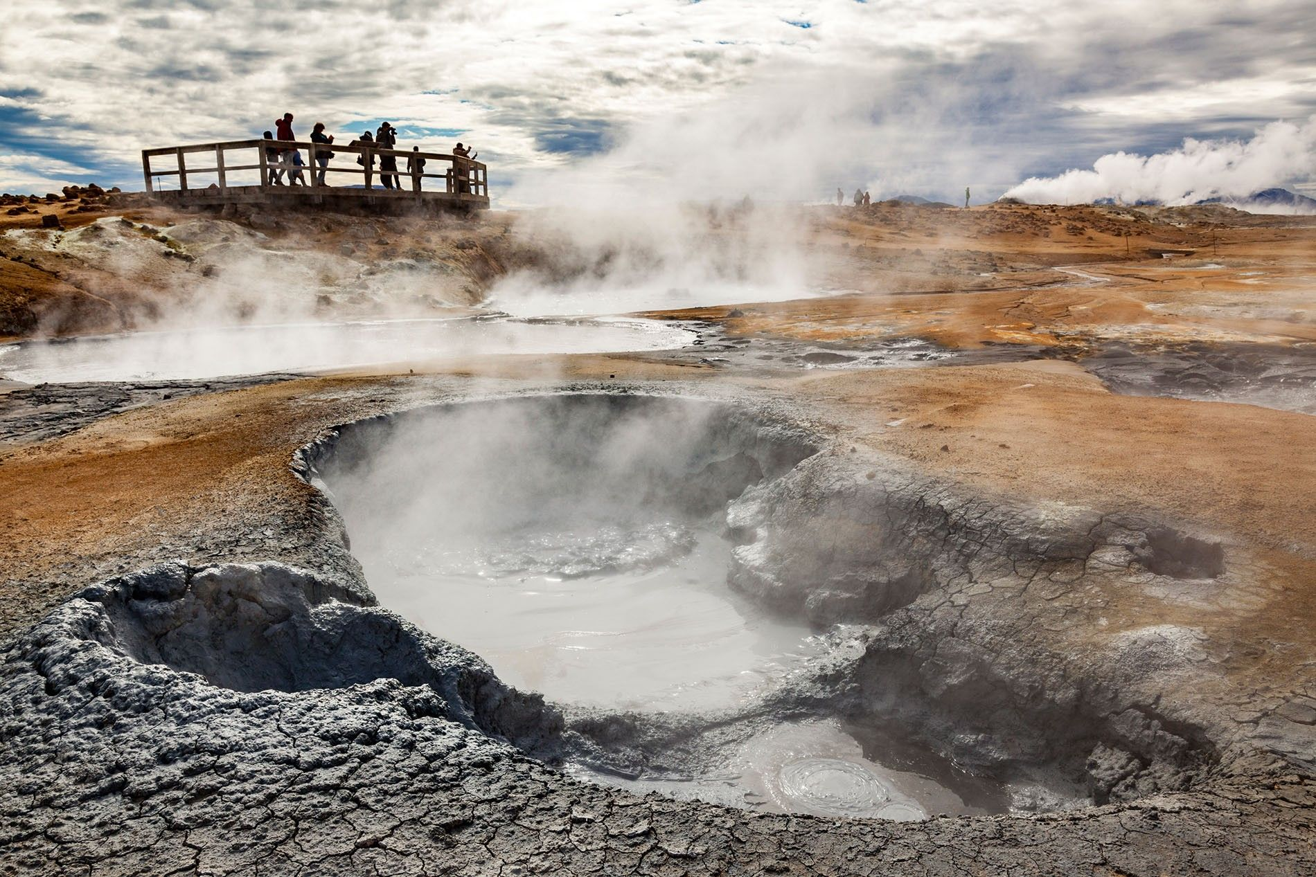 Visitors look out at steaming, sulphurous fumaroles in Námafjall, near Lake Mývatn in northern Iceland.