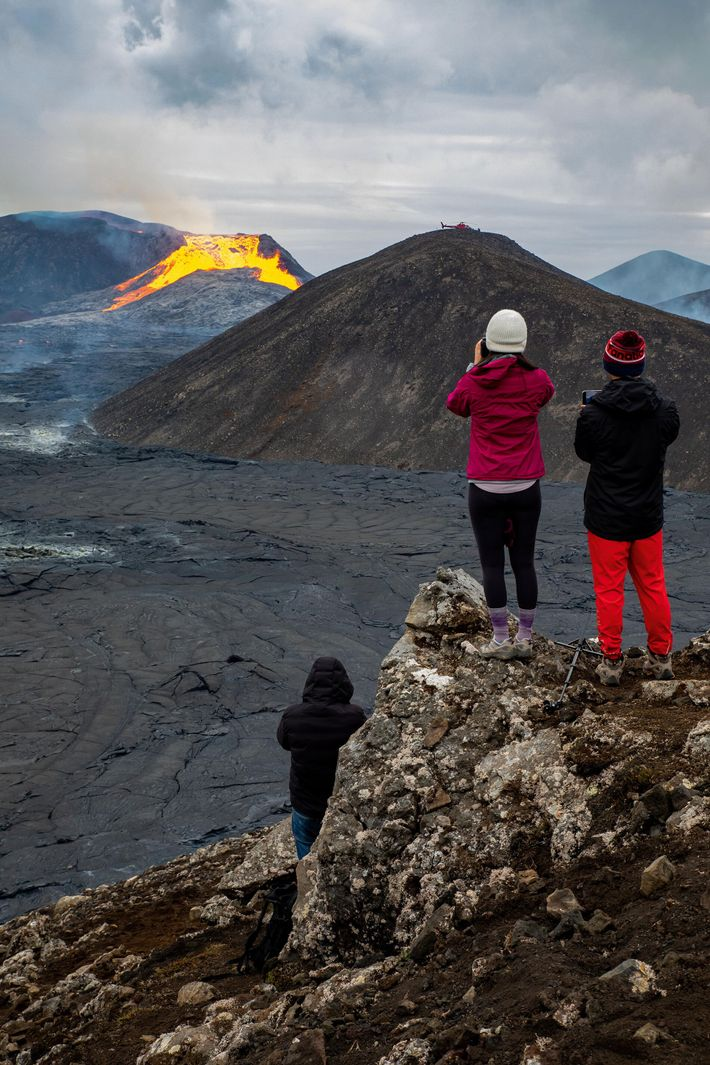Travellers watch the lava flow from Fagradalsfjall, which started erupting in March of 2021.