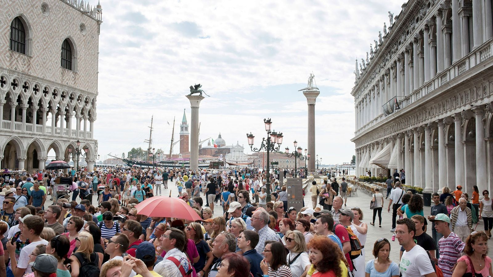 Tourists fill St. Mark's Square in Venice. One of the easiest ways to help protect popular ...