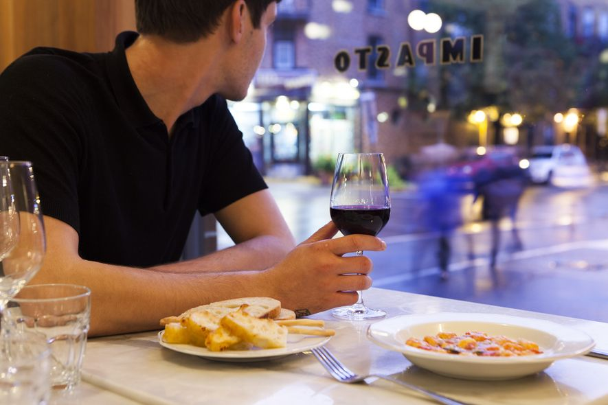 A diner enjoys a glass of wine while looking out the window at Impasto, an Italian ...