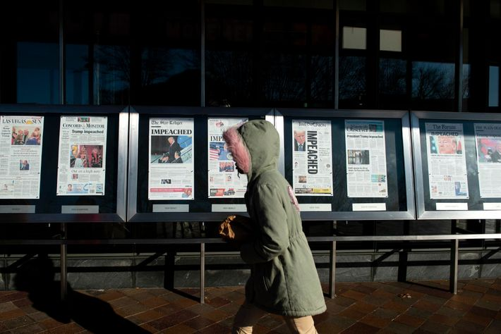 A person walks by a display of newspaper front pages from around the U.S. the day ...