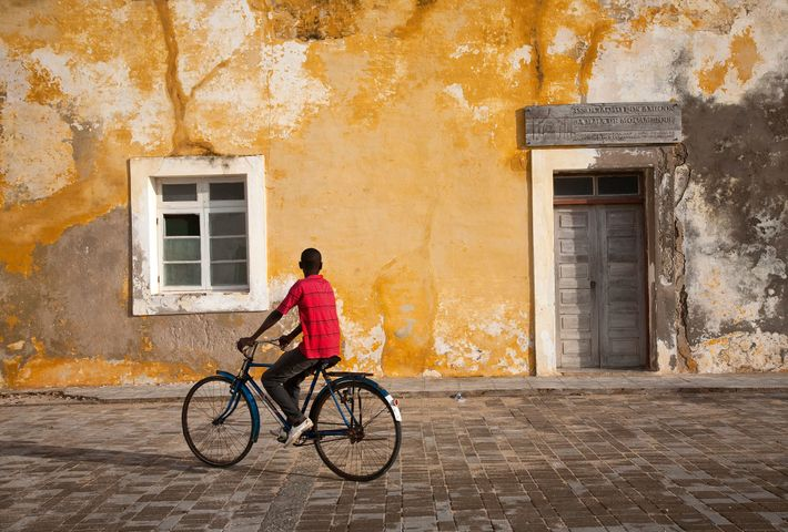 A youngster cycles through the streets of Stone Town, Island of Mozambique.