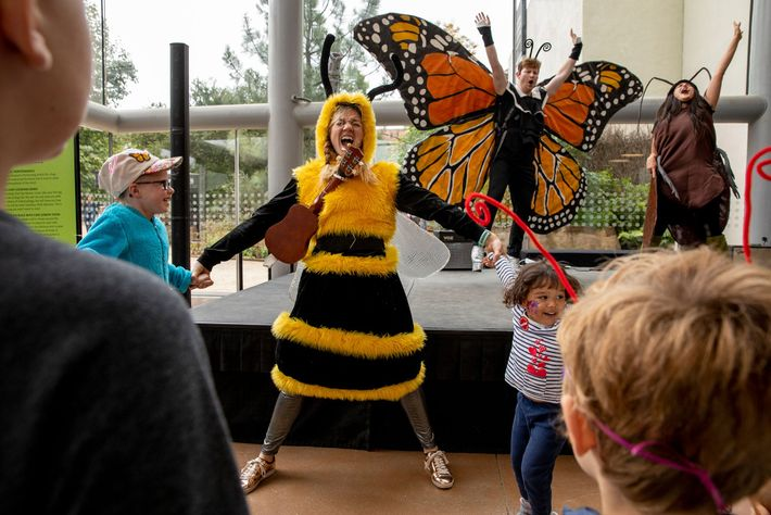 Adults dressed as a bee, a butterfly, and a cockroach perform a play for kids at ...