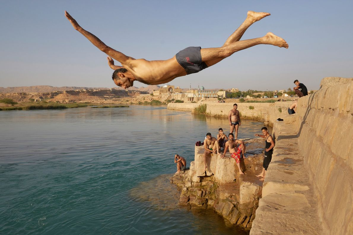 A man leaps in to the Karun River at the Iranian city of Shustar. The city's ...