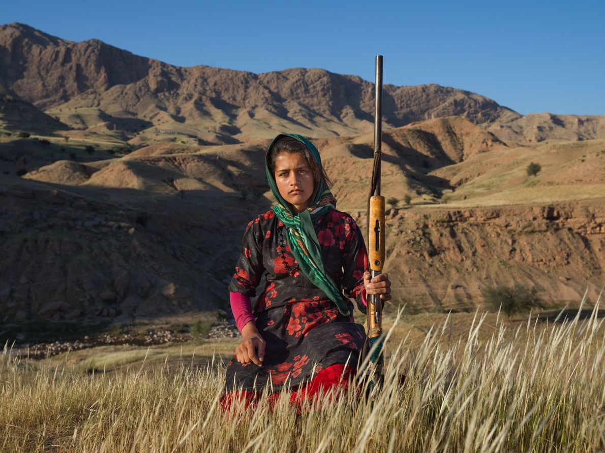 In Khuzestan Province, Masoumeh Ahmadi, 14, holds her mother's shotgun. After a woman marries, she receives ...