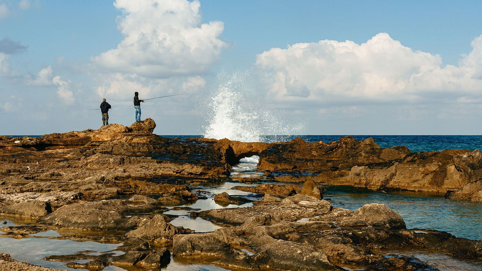 Fishermen cast lines into natural lagoons and sea pools at Achziv National Park on the shores ...