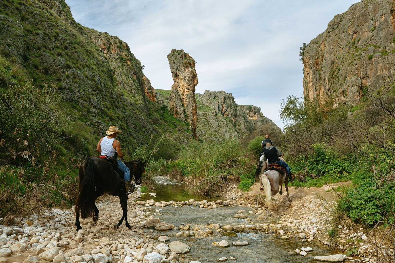A group of horse-riders on the trail below the Amud, a striking limestone pillar rising from ...