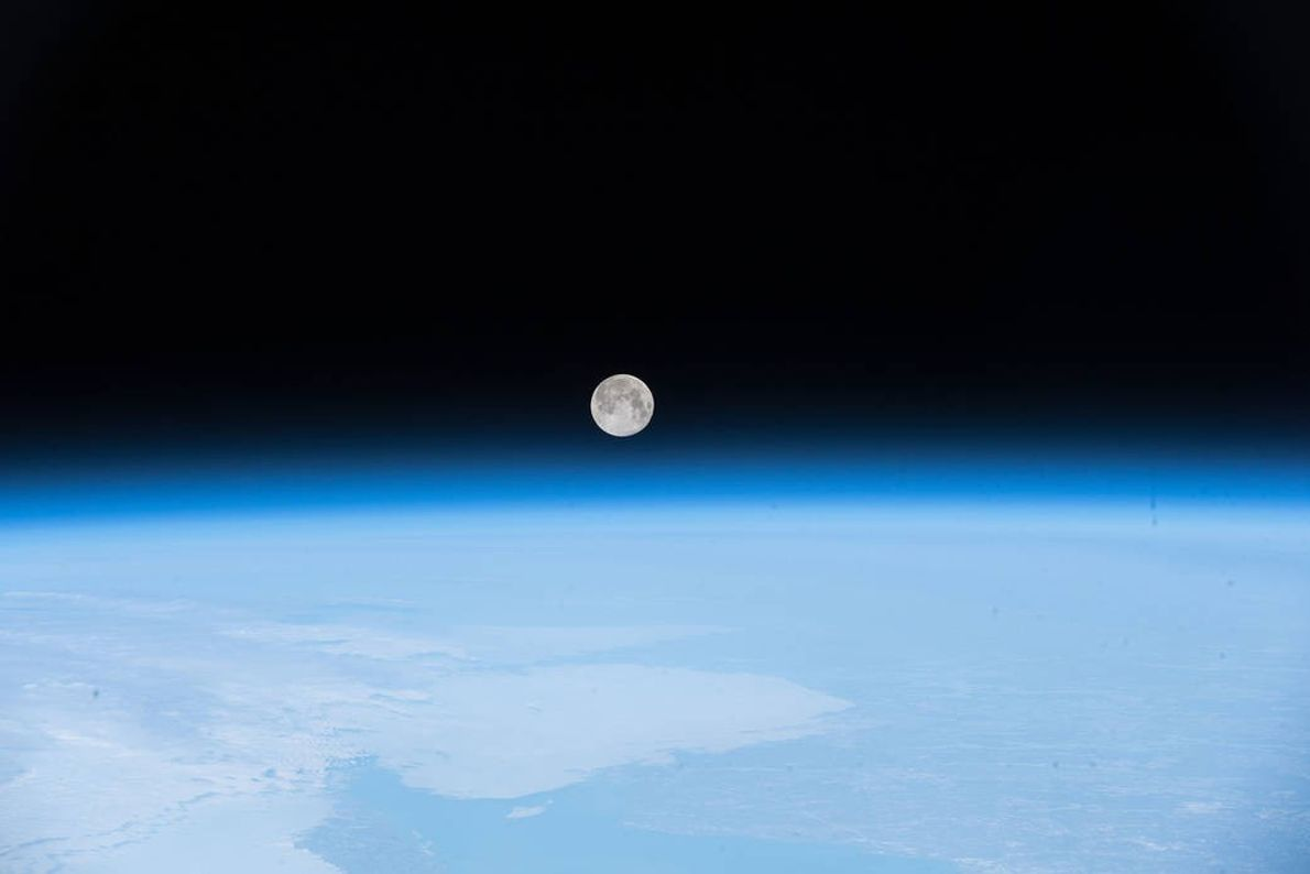 Earth's cosmic dance partner, the moon, peeks out above the blue fuzz of the atmosphere in ...