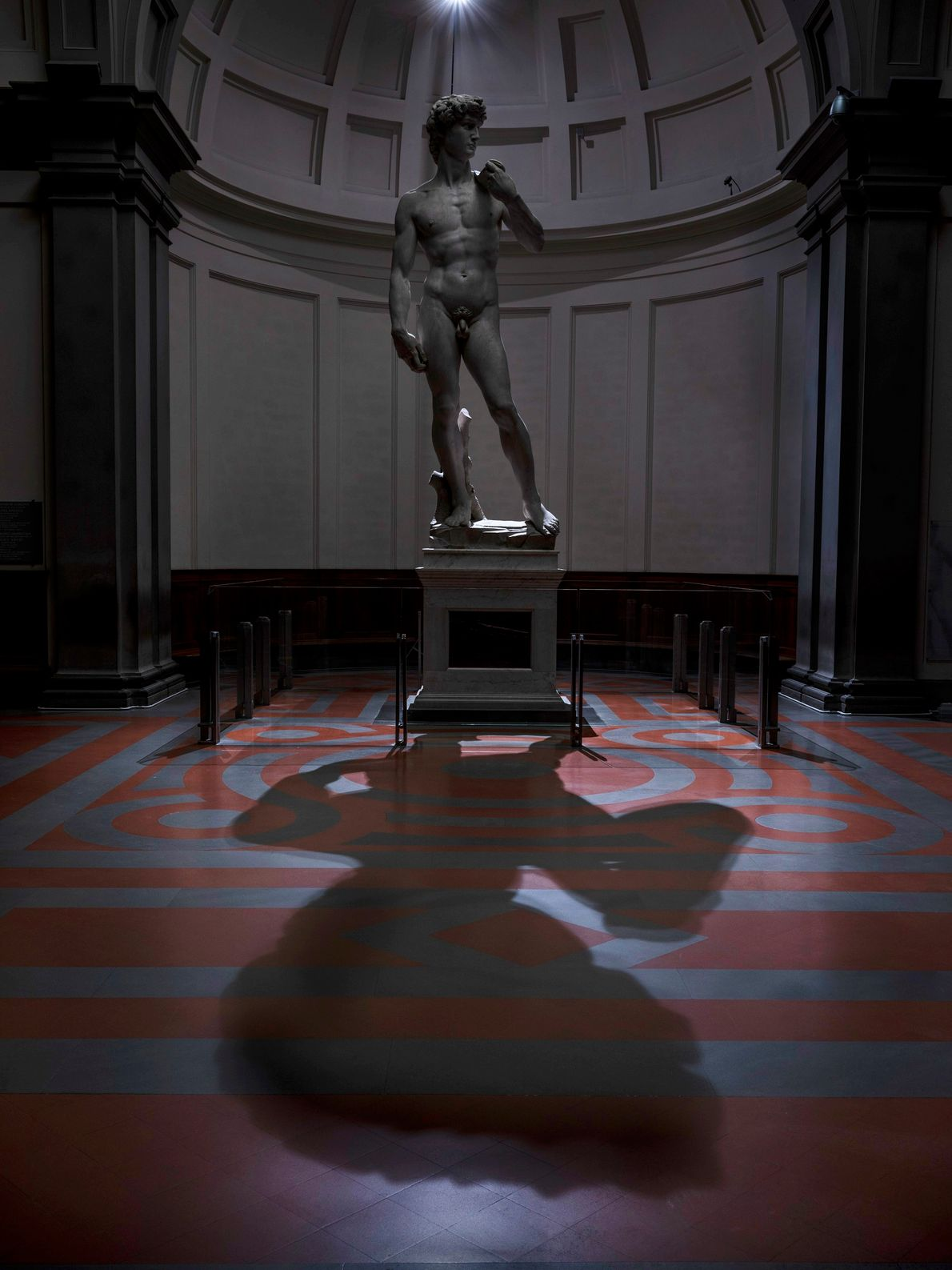 Michelangelo's iconic David (1504), poses alone with his shadow in Florence's Galleria dell'Accademia.