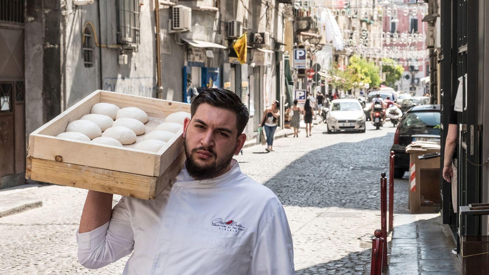 Pizza chef outside Concettina ai Tre Santi pizzeria with a tray of dough.