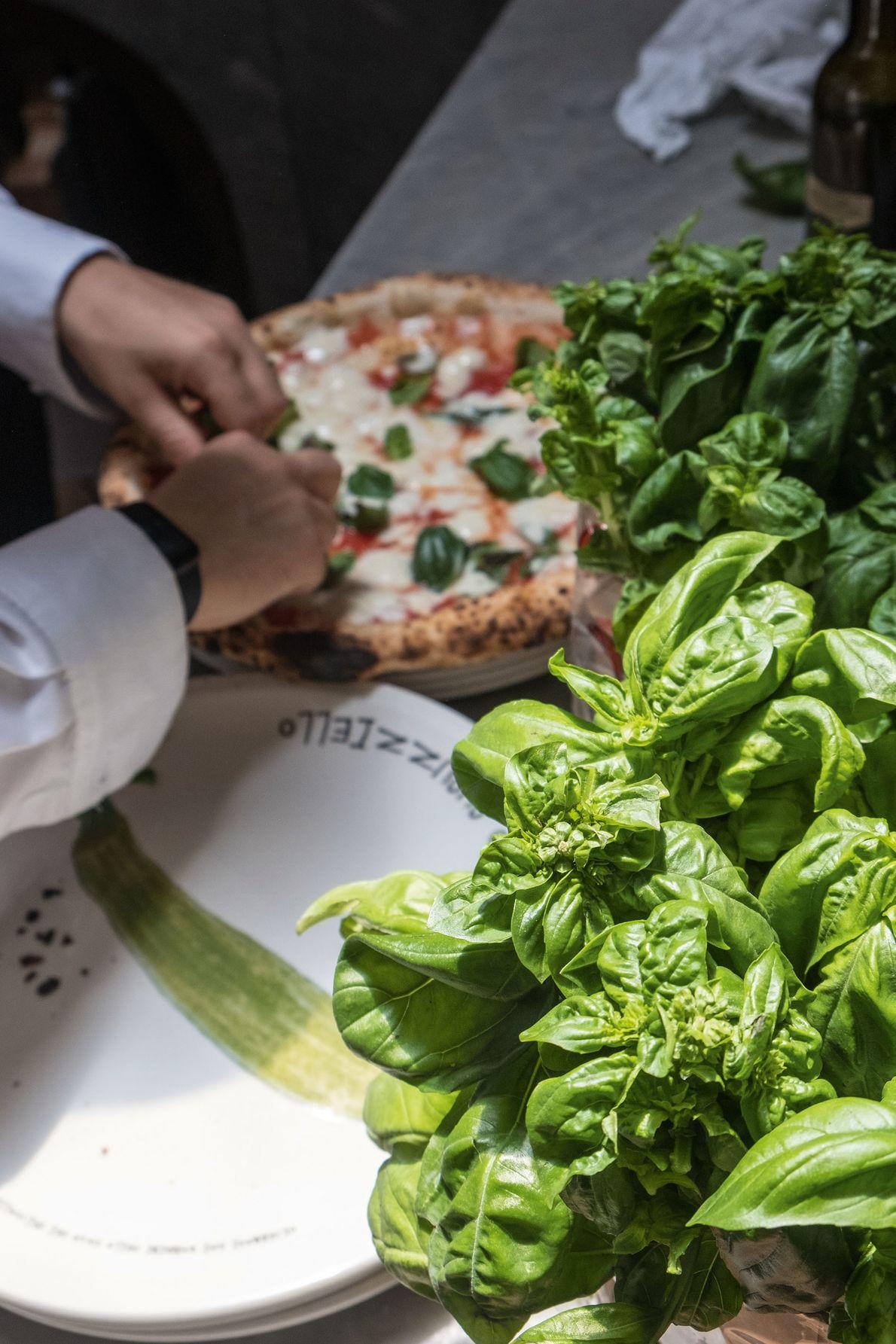 Garnishing a San Marzano pizza with fresh basil, Concettina ai Tre Santi.