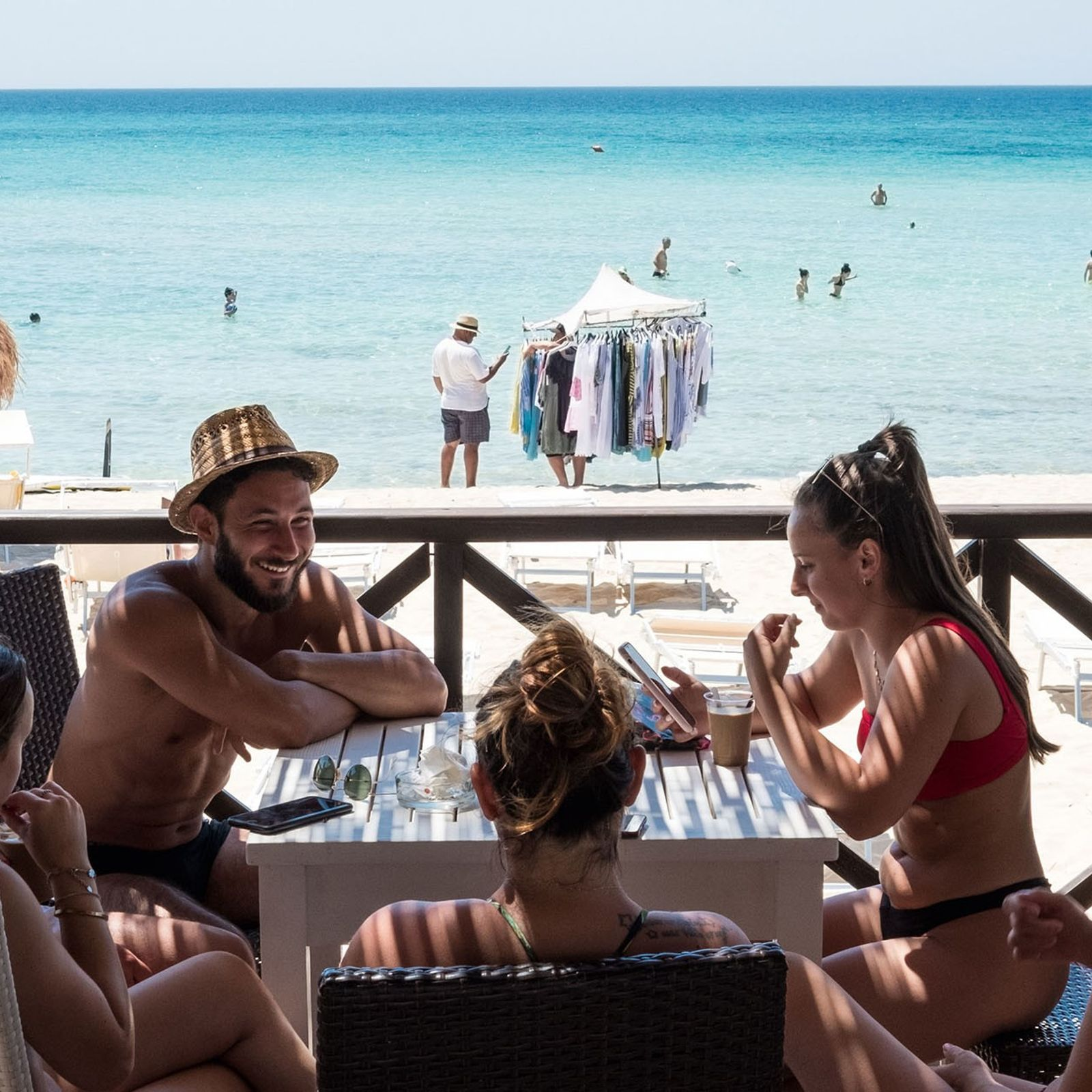 Locals share coffee at a beach bar in Punta Prosciutto, on Puglia's west coast.