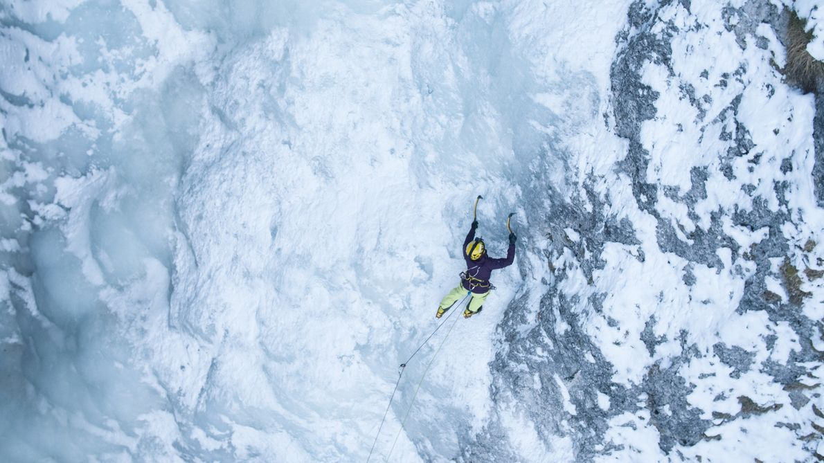 An ice climber clings to a frozen waterfall in the Italian Alps. During winter these sheltered ...