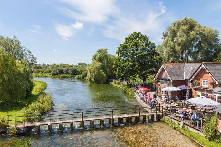 The terrace at The Mayfly pub is a prime spot for a drink, overlooking the clear, reed-rippled waters ...