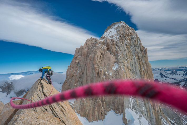 Reynolds rides the wind on the summit of Aguja Poincenoit with iconic Fitz Roy in the ...