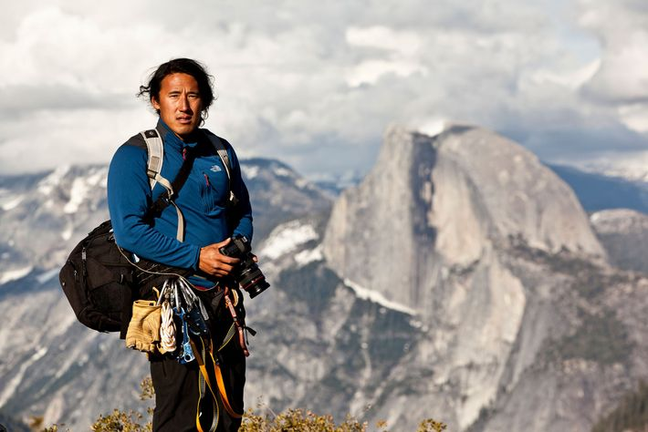 Photographer Jimmy Chin stands with his gear atop a peak in Yosemite National Park with Half ...