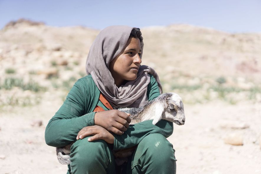 A local girl holds a goat.