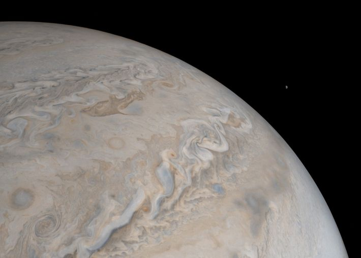 The moon Io rises over Jupiter in this image from NASA's Juno spacecraft. Slightly larger than ...