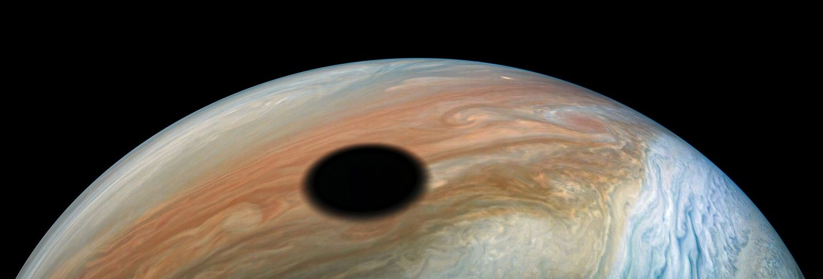 Jupiter's moon Io—a volcano world orbiting the planet once every 42 hours—casts its shadow on the ...