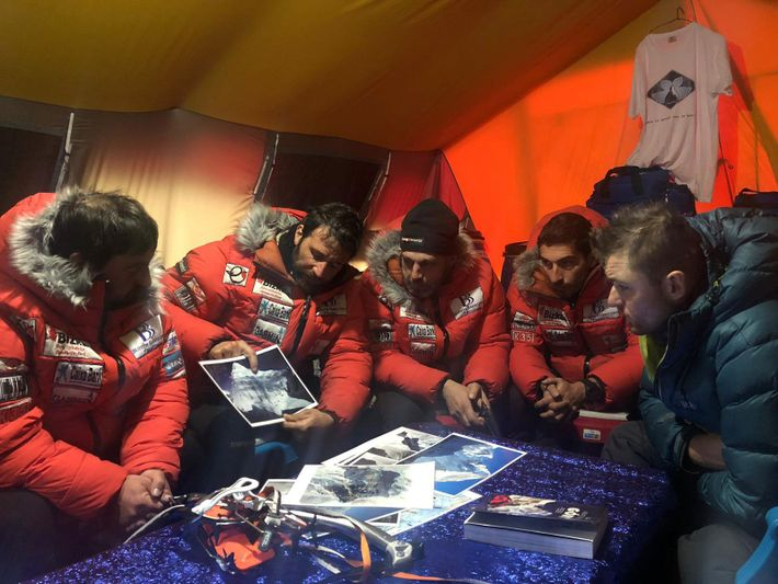 At base camp, Txikon shows his team a map of the mountain and discusses plans to ...