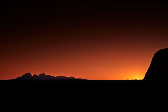 Kata Tjuta rises low on the horizon with Uluru silhouetted to the right. The Anangu ask ...
