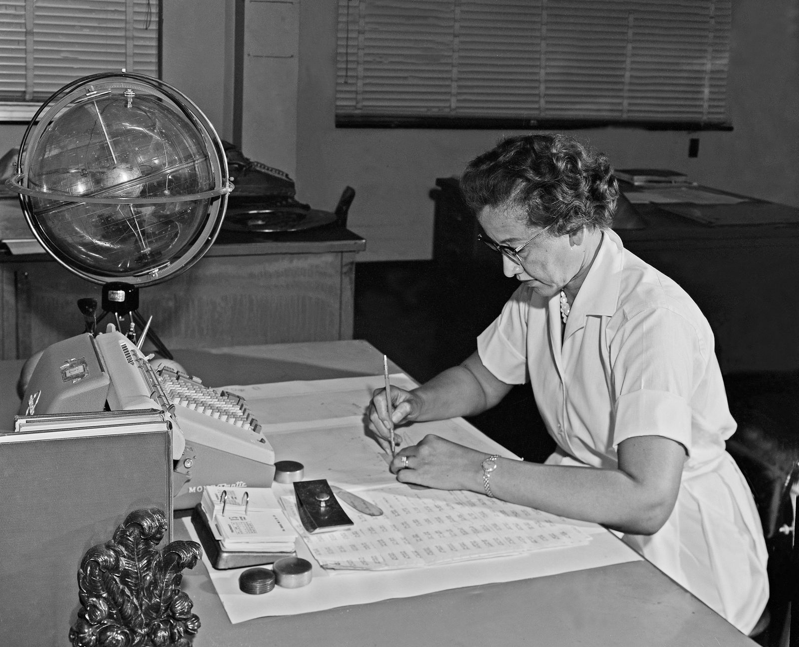 Katherine Johnson works with her slide rule and the 'Celestial Training Device' (left) that assisted her with ...