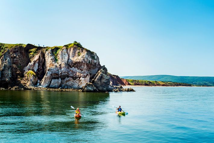 Kayakers paddle at the base of dramatic headland cliffs off the coast of the remarkable Cabot ...