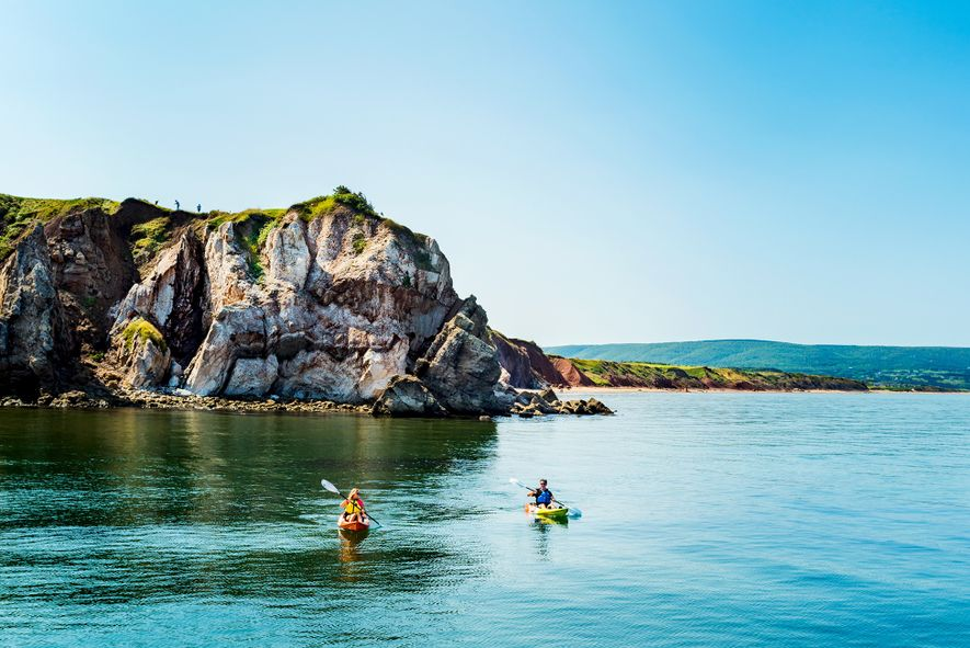 Kayakers paddle at the base of dramatic headland cliffs off the coast of the remarkable Cabot …