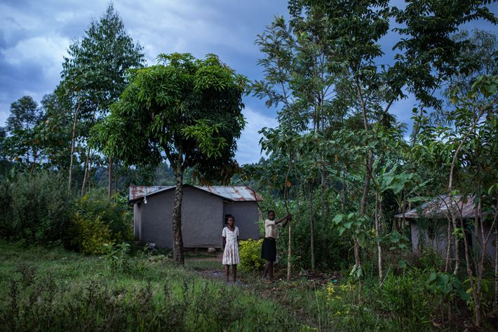 Two girls stand in front of a house in Kakamega County, Kenya. Children are at a ...