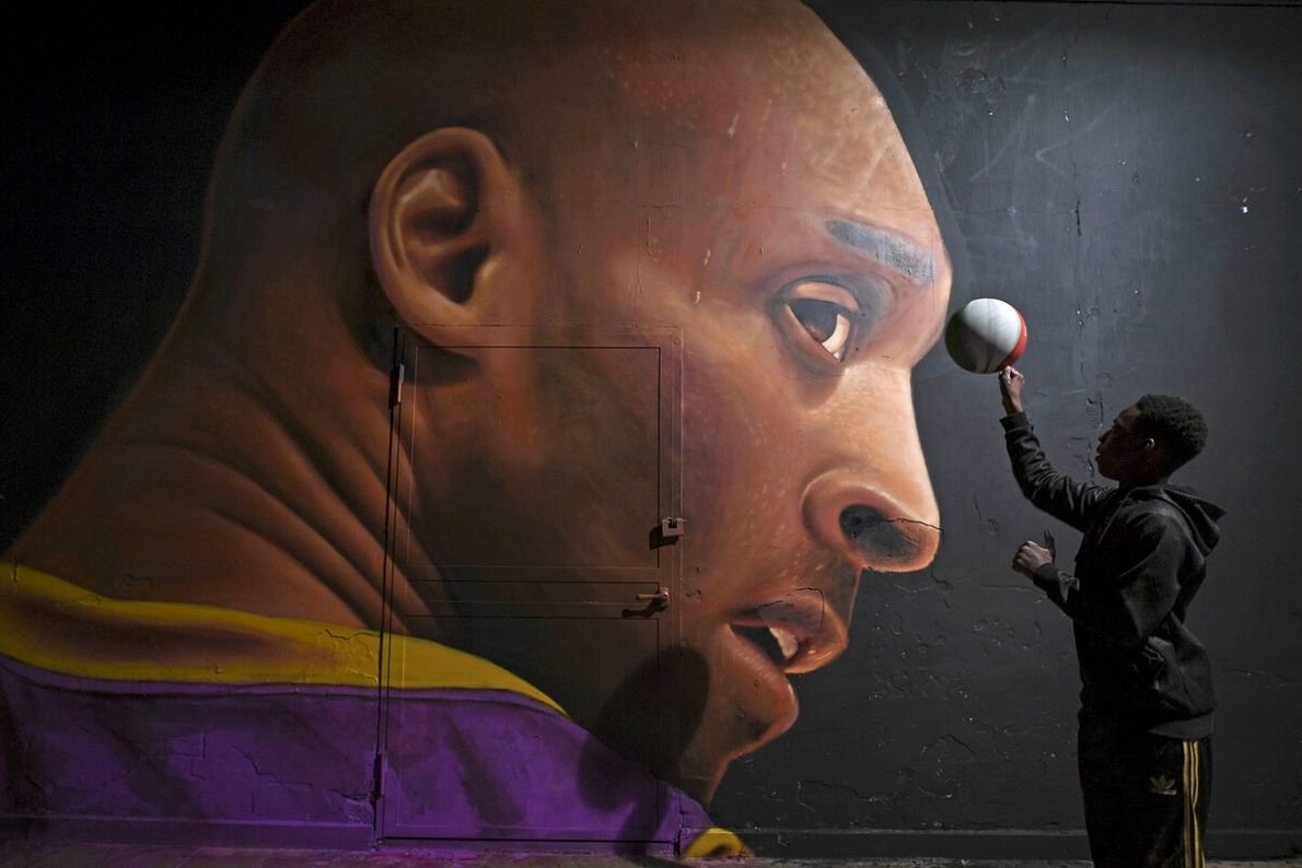 A boy plays with a basketball in Naples, Italy, in front of a mural of NBA ...