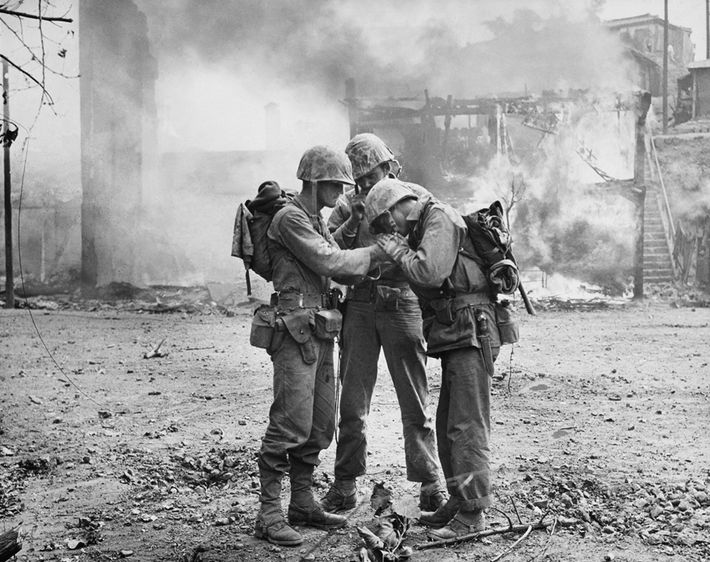 U.S. soldiers share a light for cigarettes amid smoldering ruins in Seoul, South Korea, in September ...