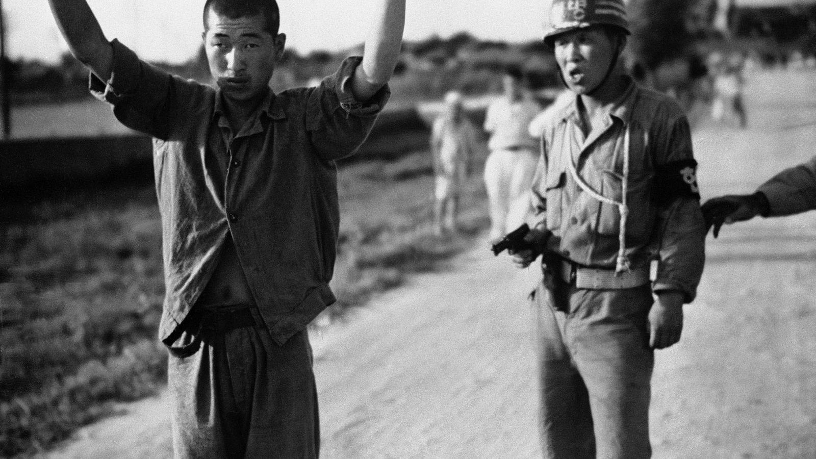 A South Korean military policeman marches a North Korean prisoner of war to a stockade in ...