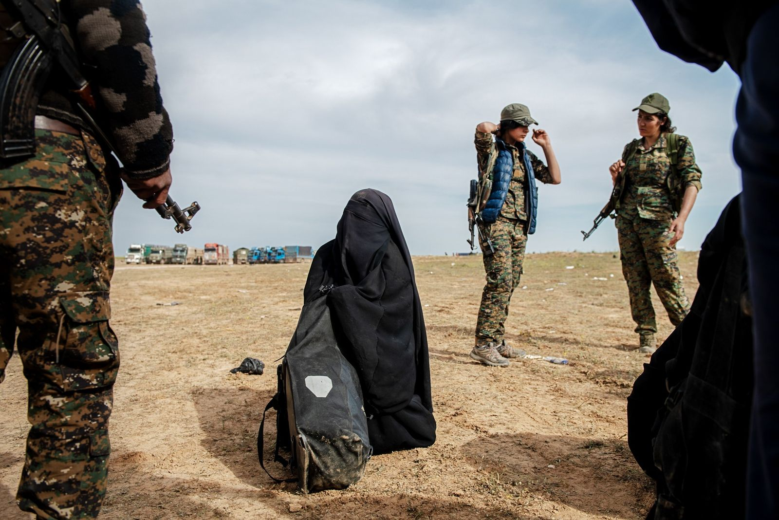 Kurdish fighters surround a surrendering woman as ISIS abandons the town of Baghouz, Syria in March. ...