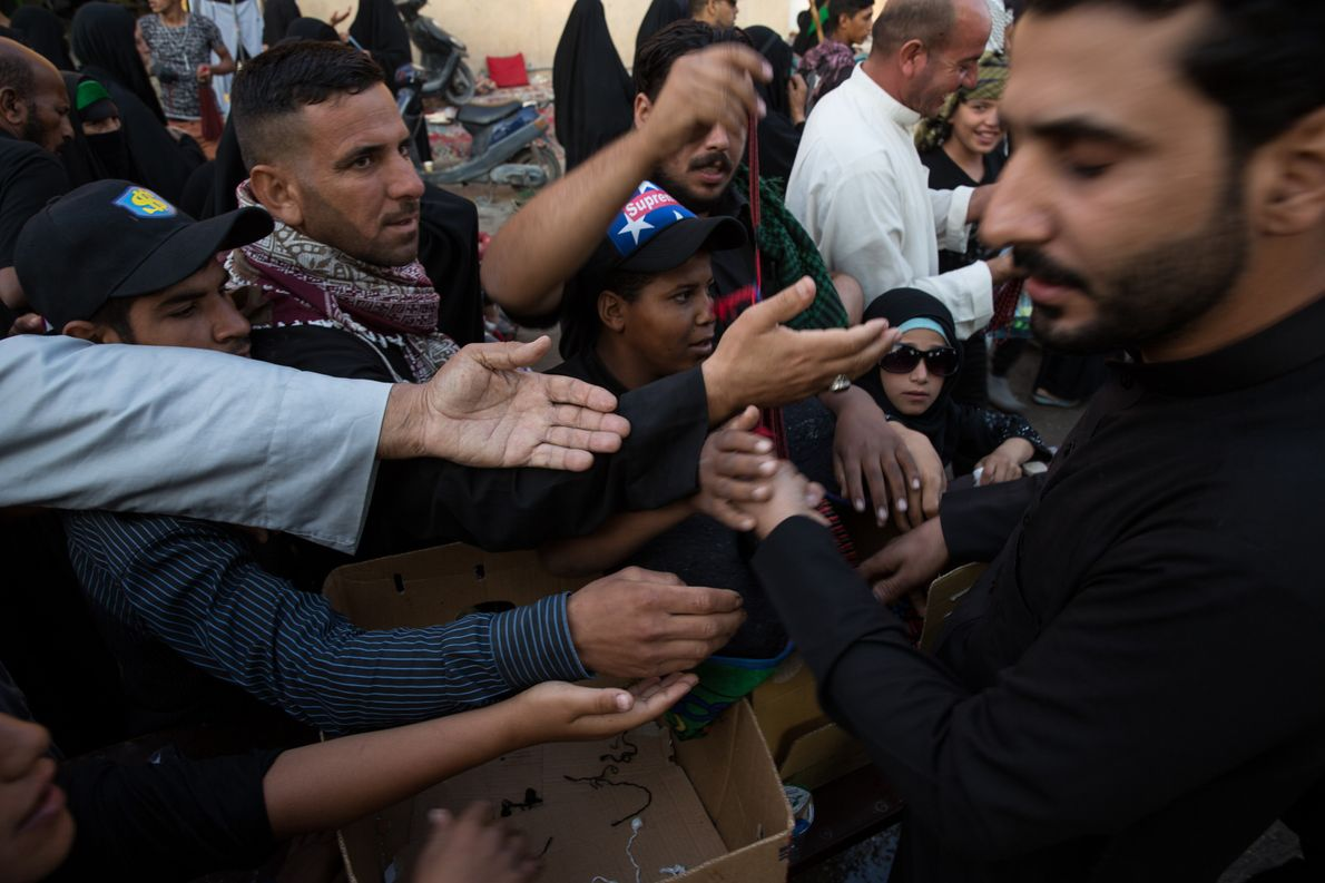 A local Karbala resident is ambushed by an onslaught of people as he hands out free ...