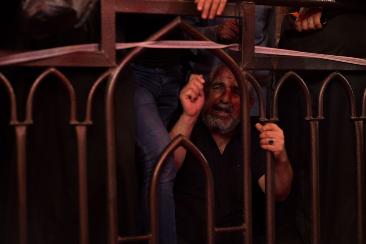 In Husayn's shrine, an emotional elderly man grips the bars that separate the crowd from the ...