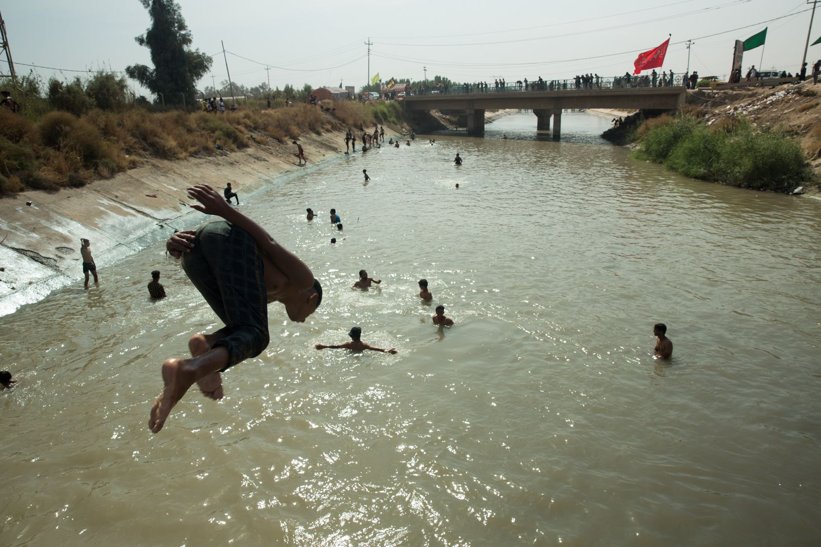 On the road young boys cool down from the scorching sun by taking a dip in ...