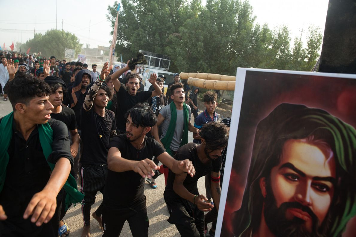 Pilgrims dance behind a cart strapped with an image of Husayn and speakers pumping out loud ...