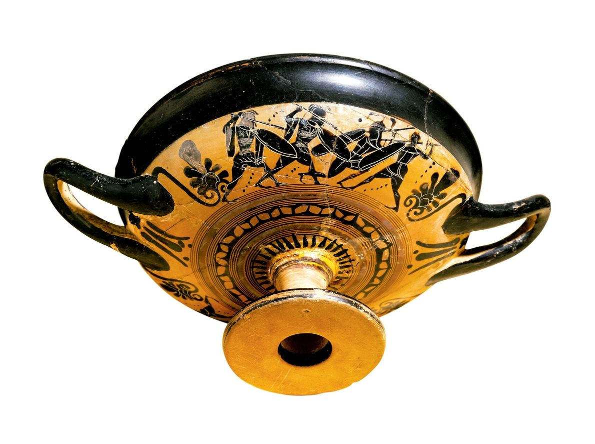 This wine cup is made in the Attic style and decorated with black figures of hoplites ...