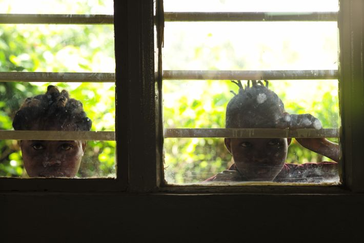 Children curiously watch preparations for the fashion show in Bukavu.
