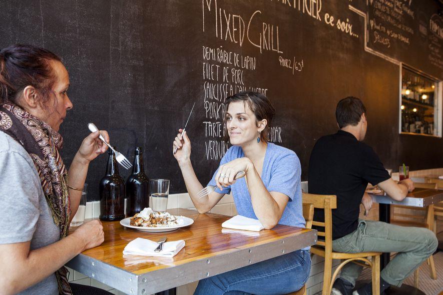 Patrons eat a meal beneath a chalkboard menu at the hip La Salle à Manger.