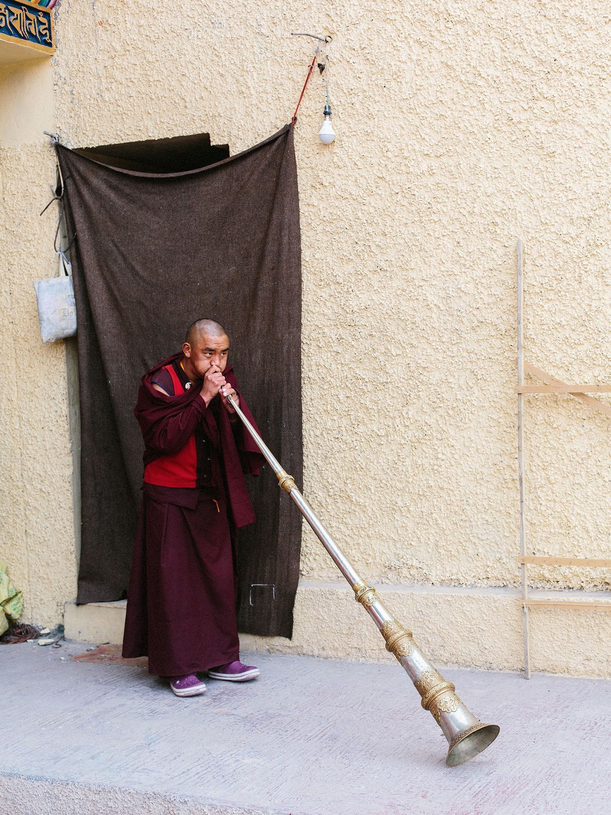 A young monk at the Karma Dupgyud Choeling Monastery blows into a ceremonial trumpet, or dungchen.